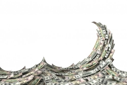 Money concept showing a wave of US dollar bills